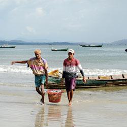 Pêcheurs déchargeant du poisson sur la plage de Ngapali au Myanmar