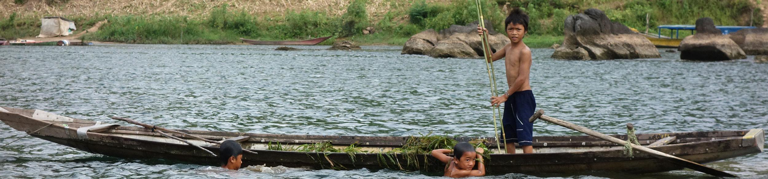 Enfants qui récoltent des racines de jacinthe d'eau à Phong Nha